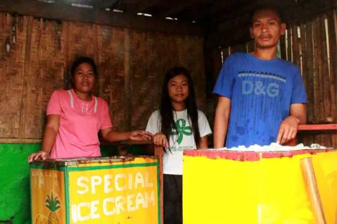 Regine (center) with her parents, Judith (left) and Reynald (right), who run an ice cream business. They prepare ice cream each day in a small area of their home in the Philippines and sell it in the community.