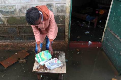 Veronica attempts to salvage her children's textbooks from their flooded home.