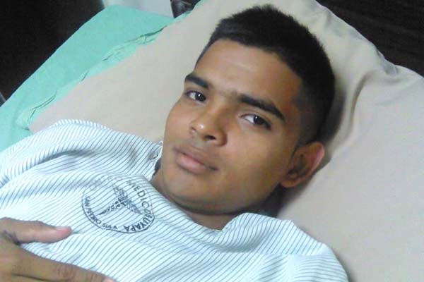A young man in Honduras laying in bed in a hospital gown.