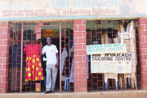 Charles welcomes customers to his tailoring business.