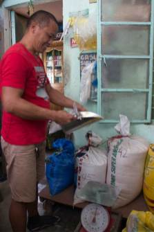 Image = Danilo prepares to measure a bag of rice for a customer.
