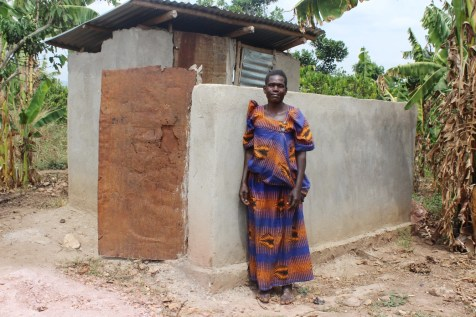 Image = Nakitende shows off the new latrine her family was able to build with the help of Unbound sponsorship.