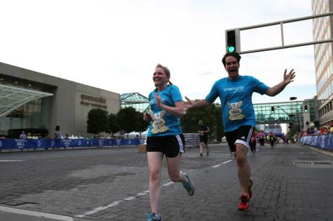 An image of two runners crossing a finish line together.
