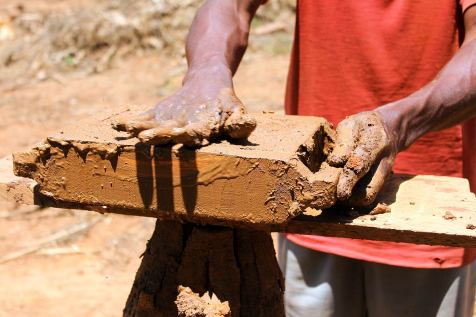 Image of the hands of a man in Uganda smoothing clay over a brick form.