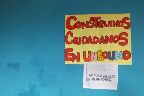 "Image = a colorful sign in an Unbound office reading ""We build citizens in Unbound"" in Spanish."