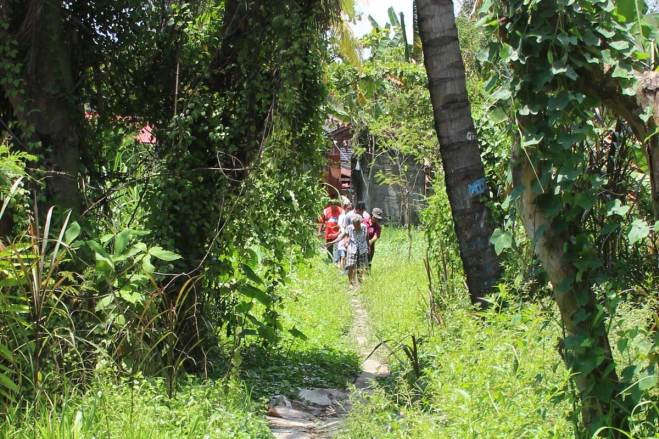 Salvacion leads Unbound staff members along the path outside her home.