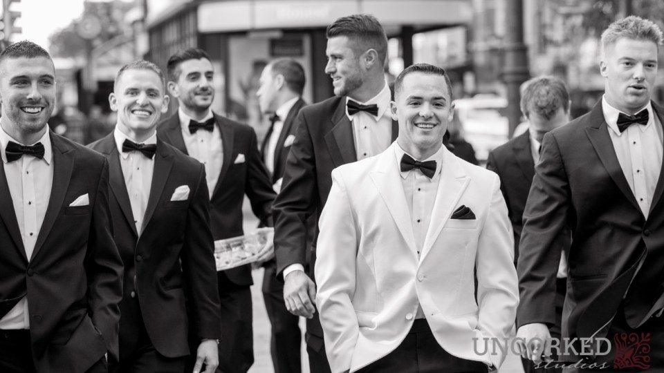 Dapper groom and groomsmen walk the streets of Philadelphia