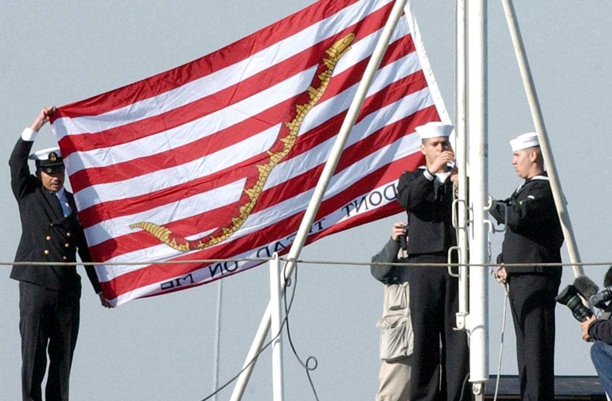 Official U.S. Navy file photo of Sailors aboard the aircraft carrier USS Kitty Hawk (CV 63) raising the Don't Tread On Me flag First Navy Jack. All ships will begin flying the First Navy Jack at morning colors on Sept. 11, 2002..