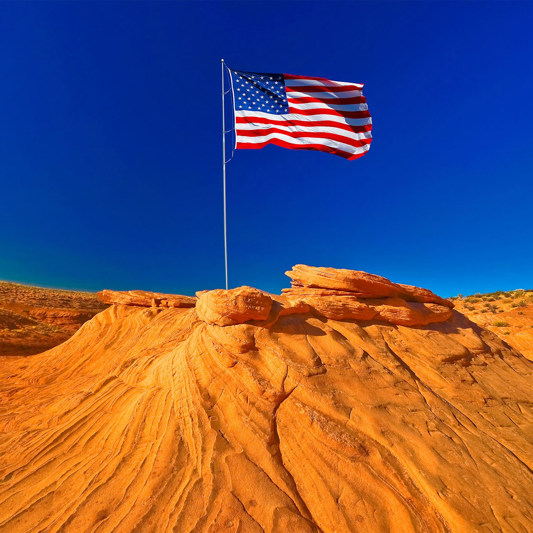 A beautiful and stunning sight of an American flag in a large, dry, barren region, usually having sandy or rocky soil and little or no vegetation.