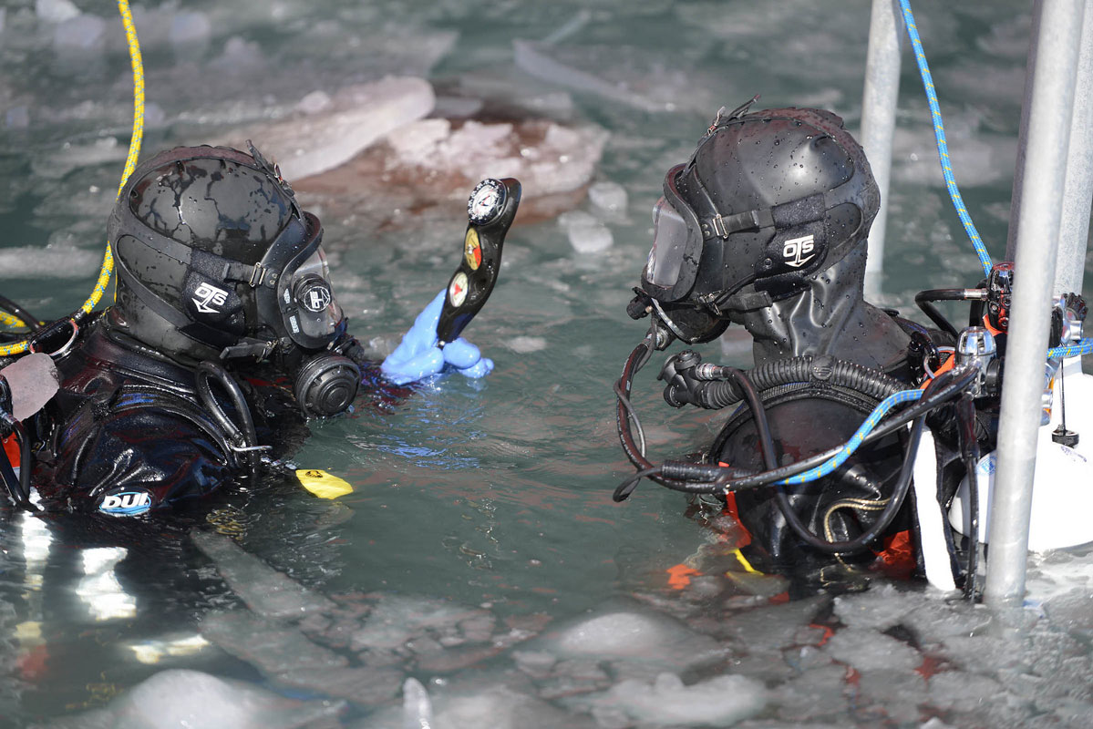 Coast Guard Petty Officer 2nd Class Garett Brada, a diver deployed aboard the U.S. Coast Guard Cutter Polar Star, checks his dive gauges before a cold water ice dive off of McMurdo Station, Jan. 19, 2017. Divers bring the option of sub-surface support for the cutter's command, in the event repairs or inspections are needed.