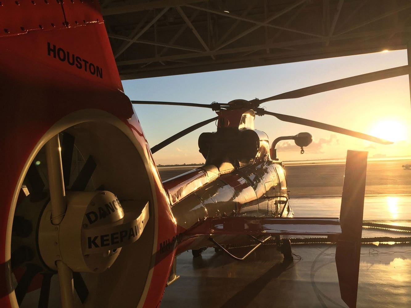 One of Air Station Houston's MH-65D Dolphin helicopters is prepped and ready to go for the day as the sun begins to rise. This helicopter represented the Coast Guard during a live hoist demonstration and a static display alongside a centennial painted MH-60T Jayhawk and a C-130 Hercules during the Wings Over Houston Air Show, which attracted over 100,000 visitors.