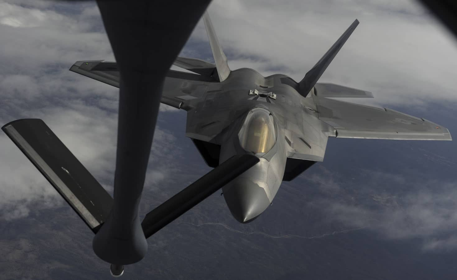 An F-22 Raptor fighter jet, assigned to the 433rd Weapons Squadron, at Nellis Air Force Base, flies to meet a KC-135 Stratotanker cargo aircraft assigned to the 509th Weapons Squadron, Fairchild Air Force Base, Washington, boom for aerial refueling over the Nevada Test and Training Range, Nevada.