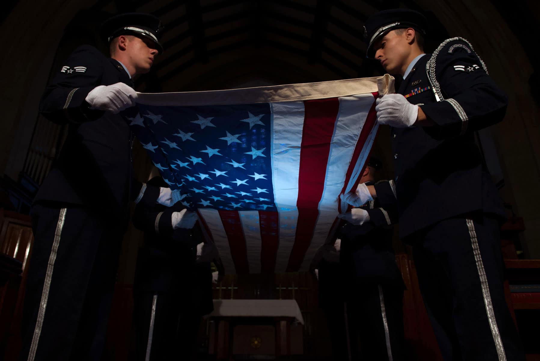 Air Force service members, assigned to the base Honor Guard, perform a flag folding ceremony at Joint Base Langley-Eustis, Va. The Old Glory flag folding ceremony is a time honored tradition that is used during Memorial Day and Veterans Day ceremonies, as well as retirements from the Armed Forces.