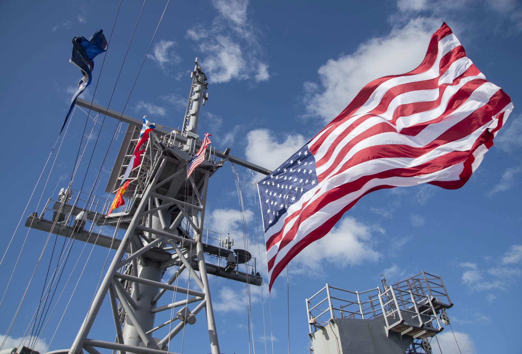 The United States Navy battle flag and battle ensign fly on the masts of the amphibious assault ship USS Bonhomme Richard (LHD 6) as the ship steams along with a Combined Amphibious Force as part of a mutli-ship sailing formation during Talisman Saber 17.