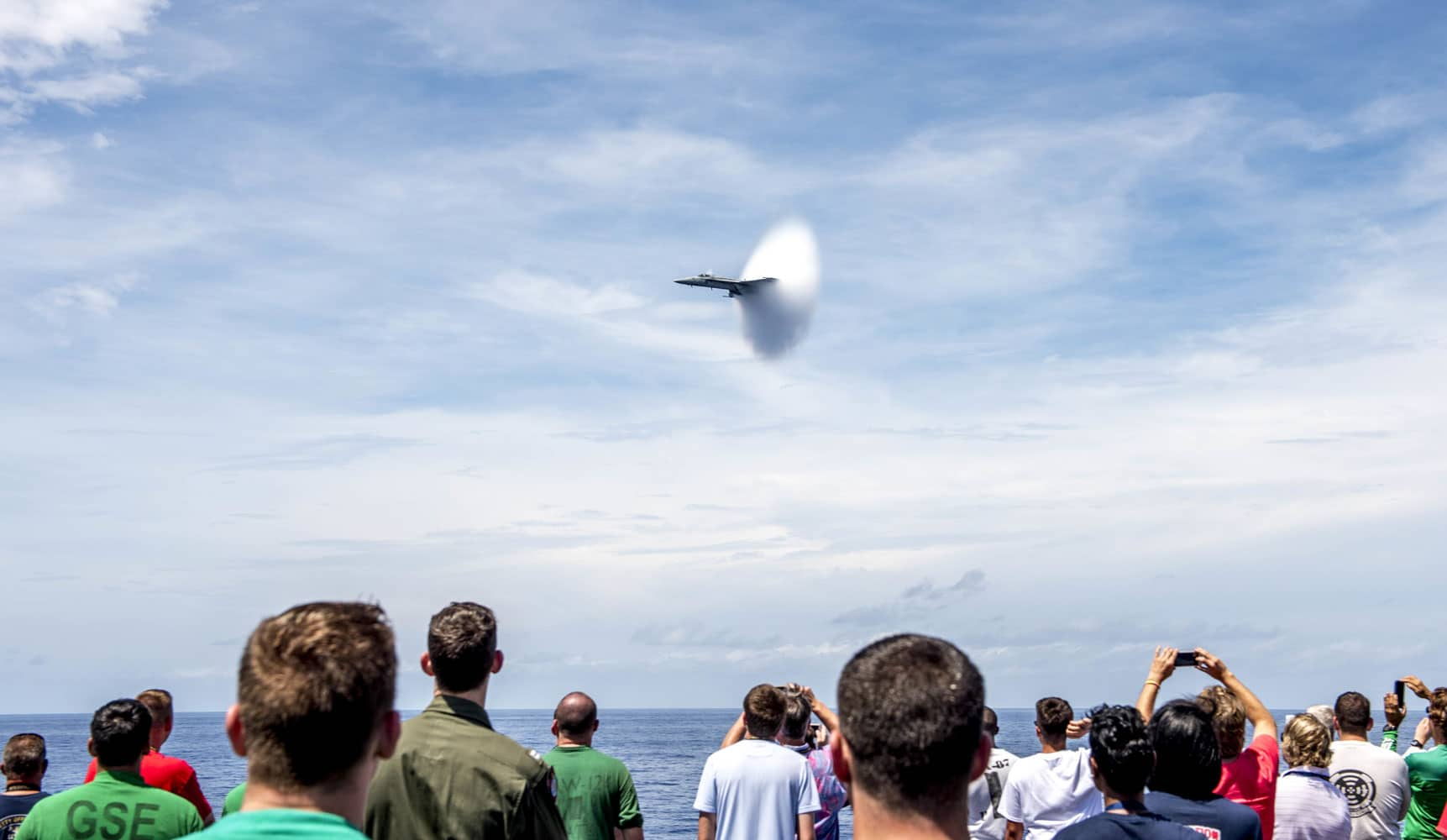 "Sailors and their guests watch an F/A-18E Super Hornet attached to the ""Tomcatters"" of Strike Fighter Squadron 31 during an air power demonstration for a tiger cruise aboard the aircraft carrier USS George H.W. Bush."