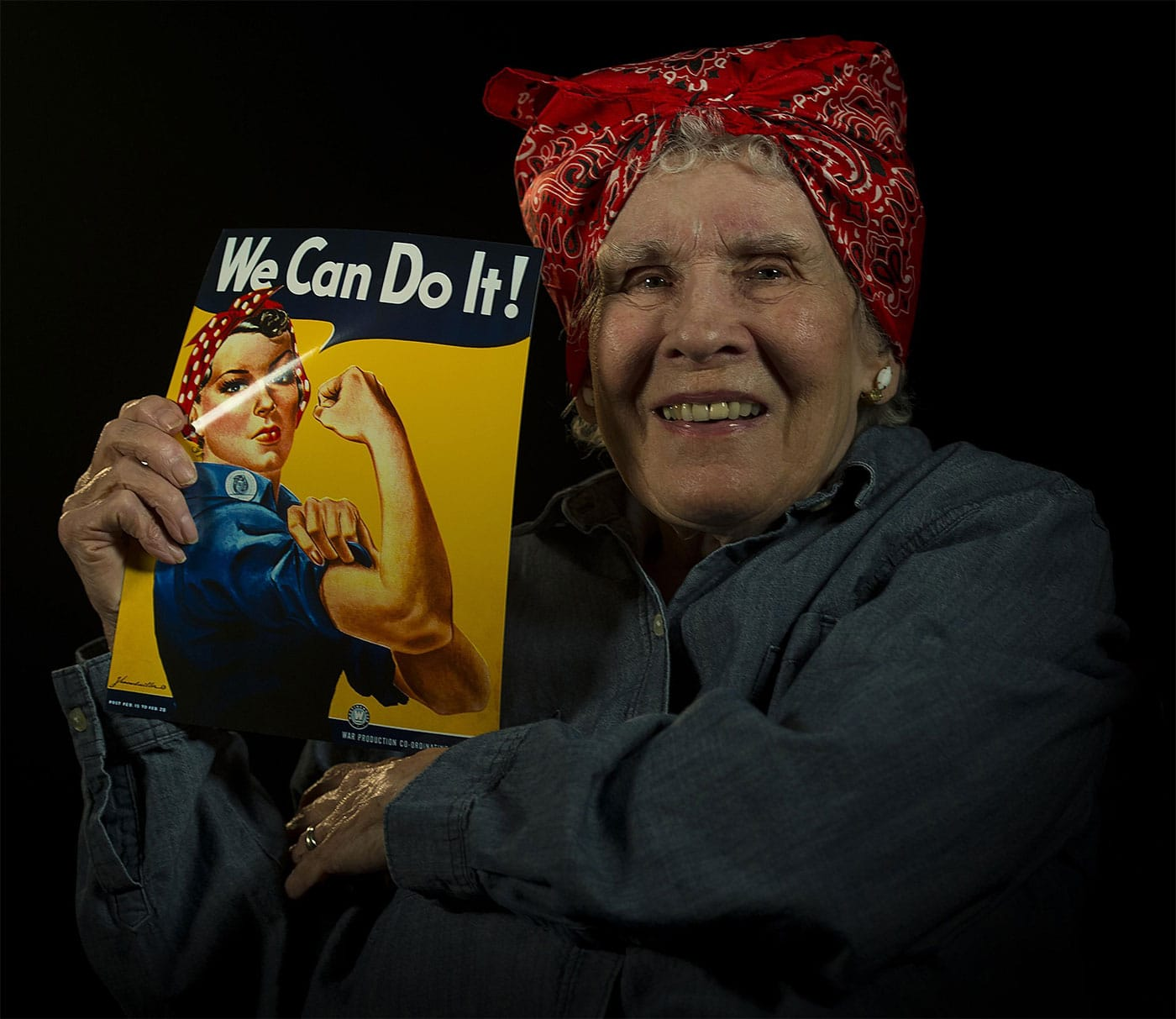 """Margaret """"Peggy"""" Wills, B-24 electrician during World War II, holds a recruitment poster at Minot Air Force Base. Wills was a """"Rosie the Riveter"""" at Holman Field in St. Paul, Minnesota."""