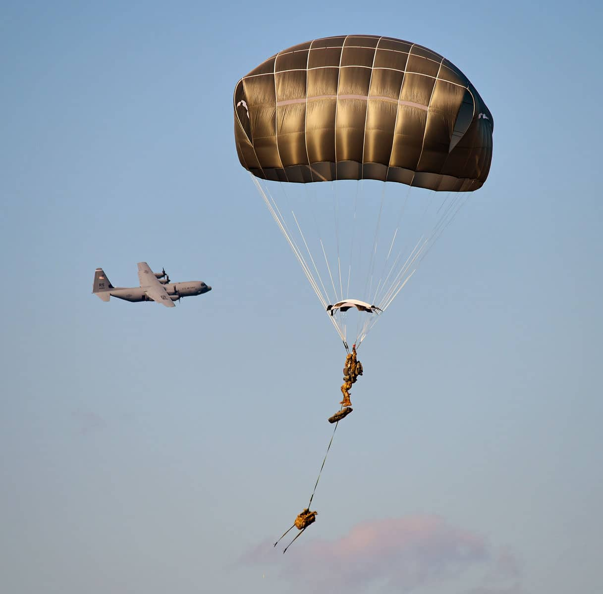 US Army Paratroopers assigned to the 173rd Brigade Support Battalion, 173rd Airborne Brigade, prepare to land after exiting a U.S. Air Force 86th Air Wing C-130 Hercules aircraft during airborne operations at Frida Drop Zone in Pordenone, Italy.