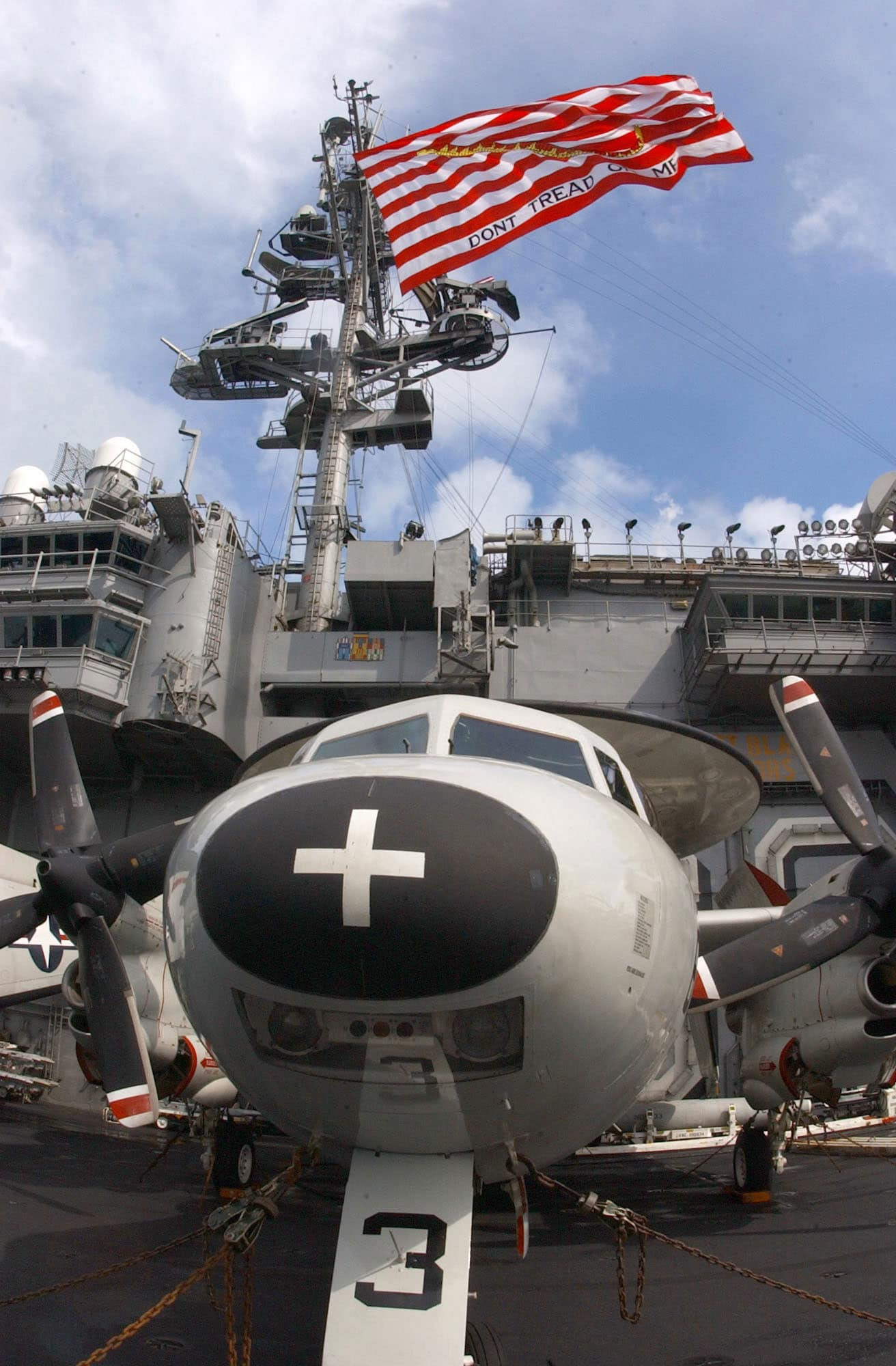 At sea aboard USS Kitty Hawk (Feb. 15, 2003) The Navys largest First Navy Jack, with the motto Dont Tread On Me, flies high above an E-2C Hawkeye belonging to the Liberty Bells of Carrier Airborne Early Warning Squadron One One Five (VAW-115), while transiting through the Straits of Malacca.