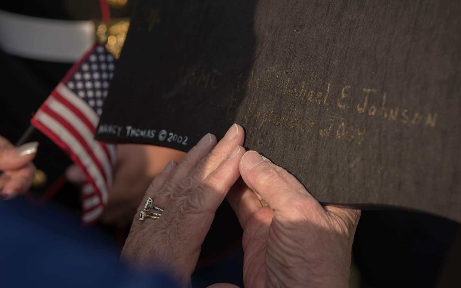 """The Honorable Angela Lee Leary, right, reads the name of the son of Claudia Johnson, Gold Star mother, from the back of a crafted flag during """"The Reading of The Names"""" at Gosnolds Hope Park, Hampton, Va., Sept. 11, 2017."""