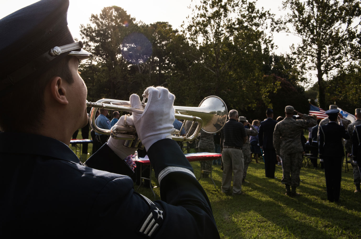 "U.S. Air Force Senior Airman Gabriel Fox, 633d Force Support Squadron ceremonial honor guardsmen, sounds the bugle playing taps during ""The Reading of The Names"" at Gosnolds Hope Park, Hampton, Va., Sept. 11, 2017."