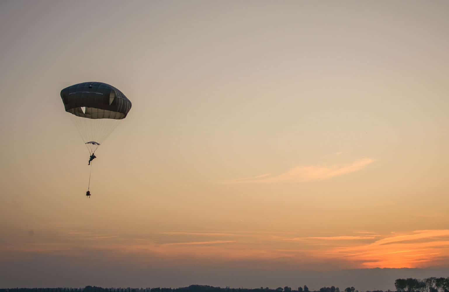 A paratrooper from the 173rd Airborne Brigade floats to the landing zone in northern Italy.