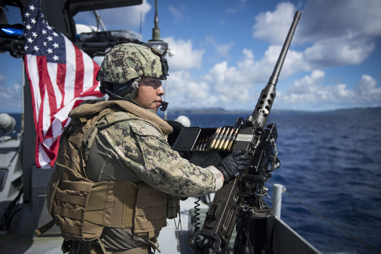 Jairo Diaz mans a United States Navy 50-caliber machine gun aboard a MK VI patrol boat while providing high value asset protection for the aircraft carrier USS Theodore Roosevelt as it transits to Apra Harbor, Guam.