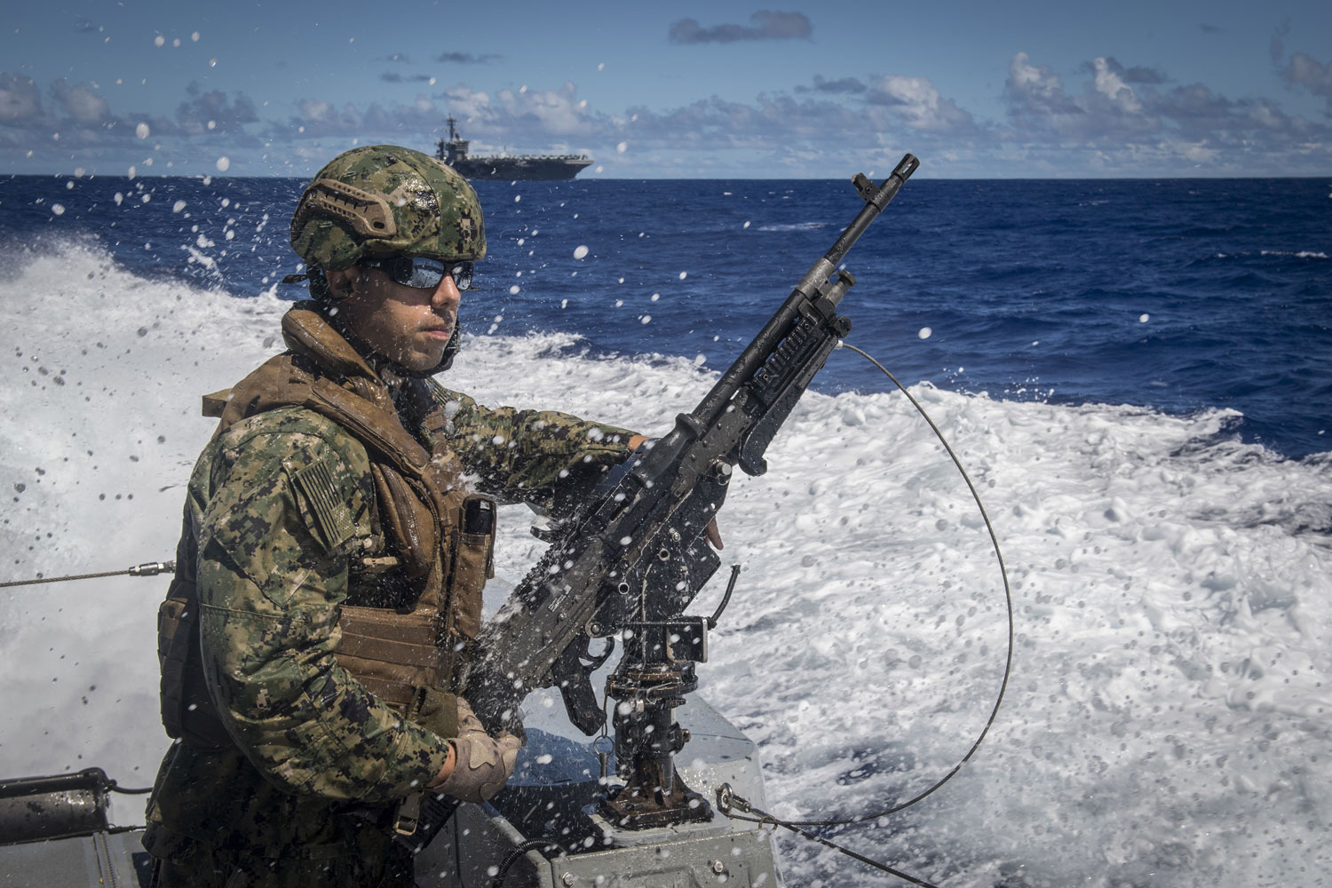 U.S. Navy Hospital Corpsman 2nd Class Jesse Smith, assigned to Coastal Riverine Squadron (CRS) 2, mans an M240G machine gun aboard a MK VI patrol boat while providing high value asset protection for the aircraft carrier USS Theodore Roosevelt (CVN 71) as it transits to Apra Harbor, Guam.