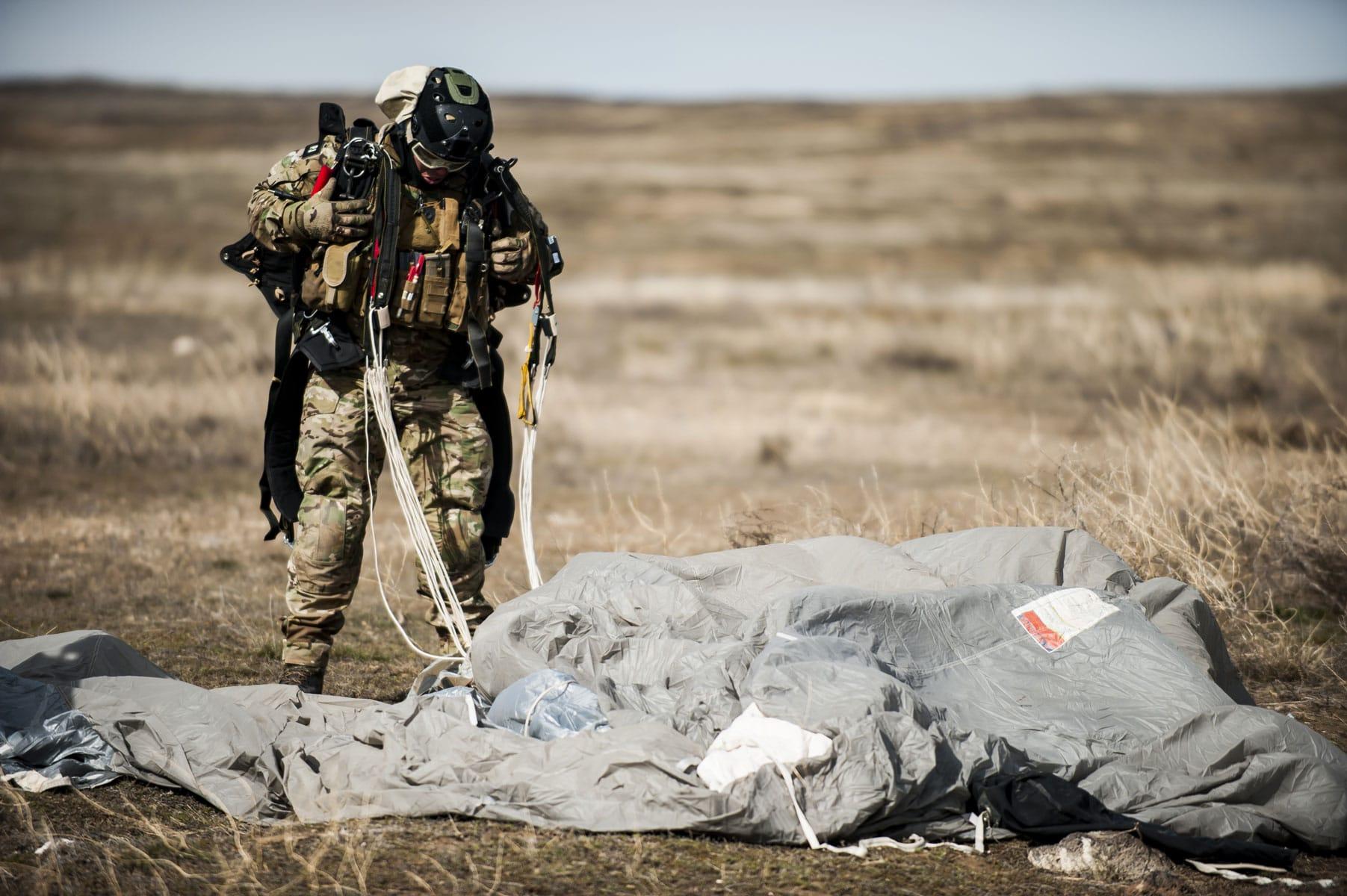 A pararescueman with the 308th Rescue Squadron, unbuckles his parachute.