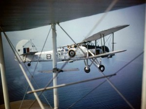 Close-up of a Fairey Swordfish Mark II, HS 545'B', in flight as seen through the struts of another aircraft.