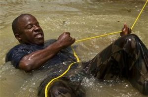Constable Allen Abbott of the Royal St. Lucia Police Force's Special Service Unit tries to pull himself to shore while practicing swift-water rescue procedures that were taught by U.S. Air Force pararescuemen. (U.S. Air Force photo/Staff Sgt. Bennie J. Davis III)