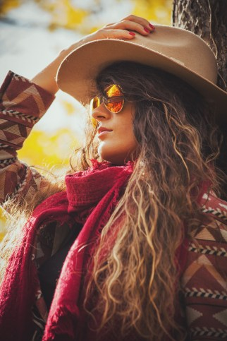 young woman wearing hat, sunglasses, red scarf and jacket, outdo