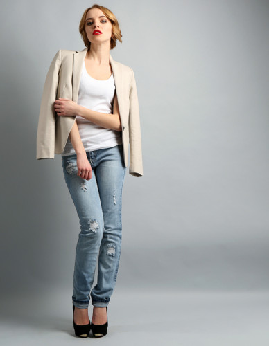 Beautiful young woman in jacket and jeans posing on light backgr
