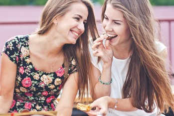Two female friends have fun time outdoors in Russia, one girl bites chocolate and hands wrapper, another one just smiling, lifestyle shot