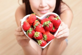 strawberry - Woman smiling with strawberry on wooden floor background focus on fruit asian beauty model