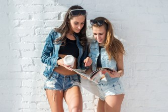Two beautiful girls friends reading the magazine wearing sunglasses and denim jeans jackets and shorts urban street casual style.