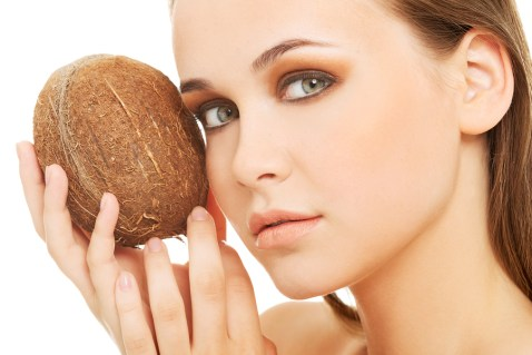 Attractive young woman with coconut. Closeup. Isolated on white.