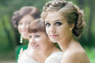 Beautiful bride with bridesmaids looking at the camera