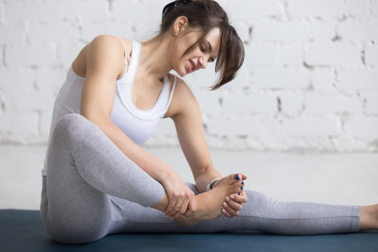Beautiful young woman feeling pain in her foot during sport workout indoors. Close-up. Focus on hands