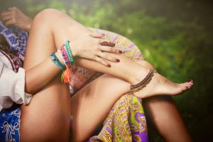 woman hand and legs with boho style colorful bracelets and ring closeup outdoor shot in garden sit on armchair