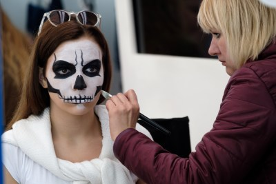 Moscow, Russia - September 10, 2016: Artist applies skull make-up for guest of City Day celebration in Park of Legends at day time