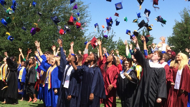 new graduates throwing caps into the air