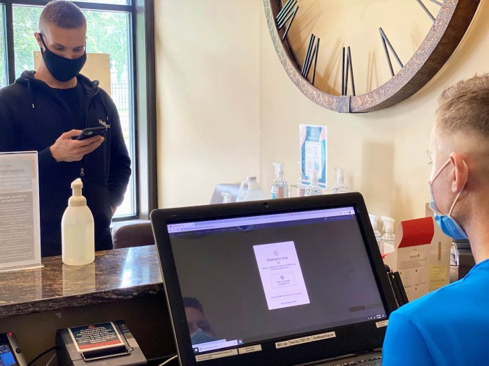 customer at front desk checking out on his phone with Vagaro's COVID-Clean Checkout