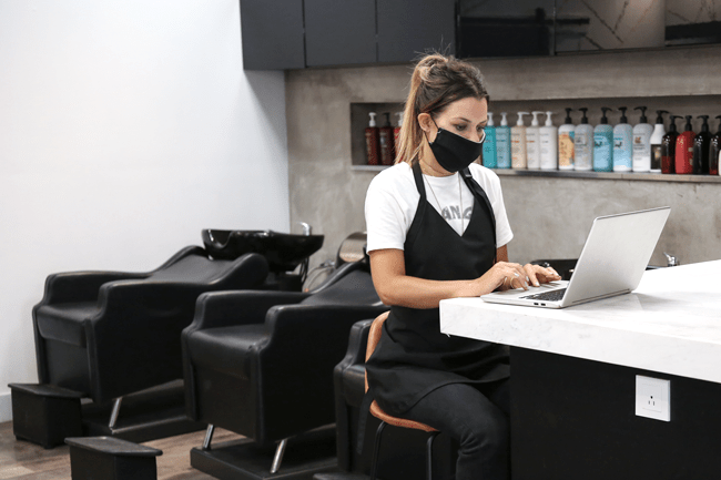 stylist in a salon at a laptop