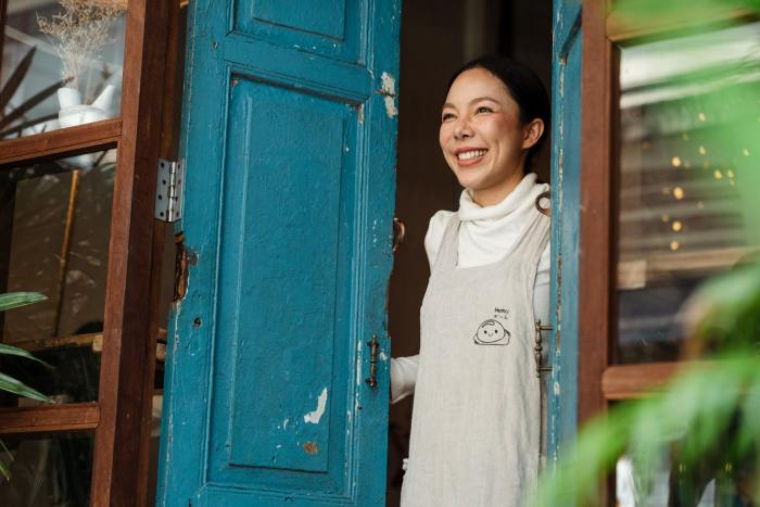 a woman smiling at the doorstep of her business