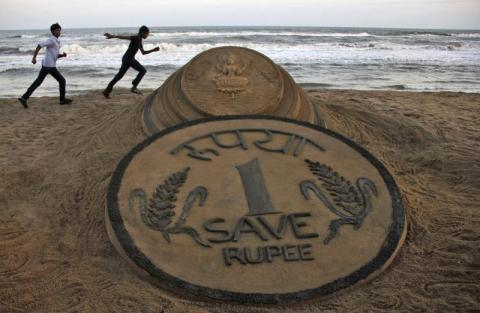 Boys run near a sand sculpture of the Indian Rupee created by Indian sand artist Sudarshan Pattnaik at golden sea beach at Puri