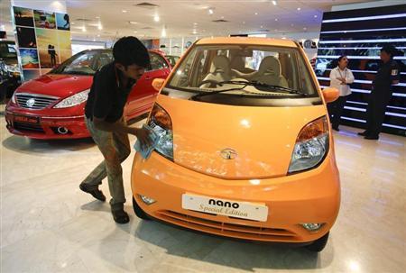 A showroom attendant cleans a Tata Nano car at their flagship showroom in Mumbai