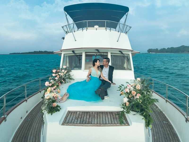 A deck of a boat with wedding flowers and a couple seated in the middle