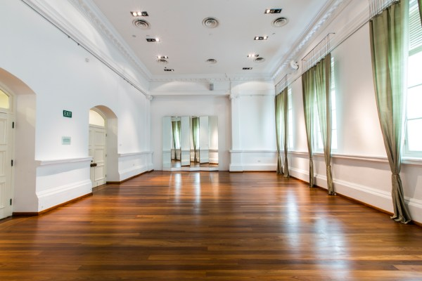multifunctional event space with wooden floor and natural sunlight from the window