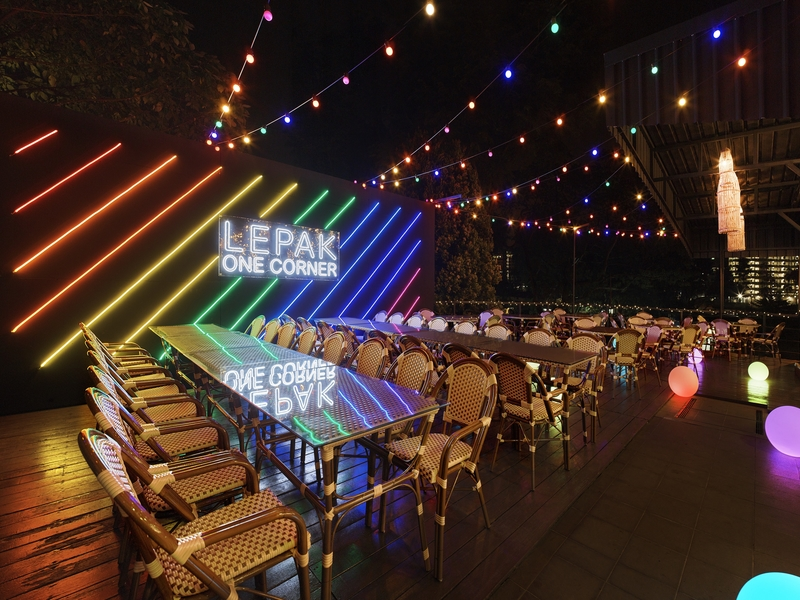 outdoor restaurant with wicker chairs and colourful hanging light bulbs