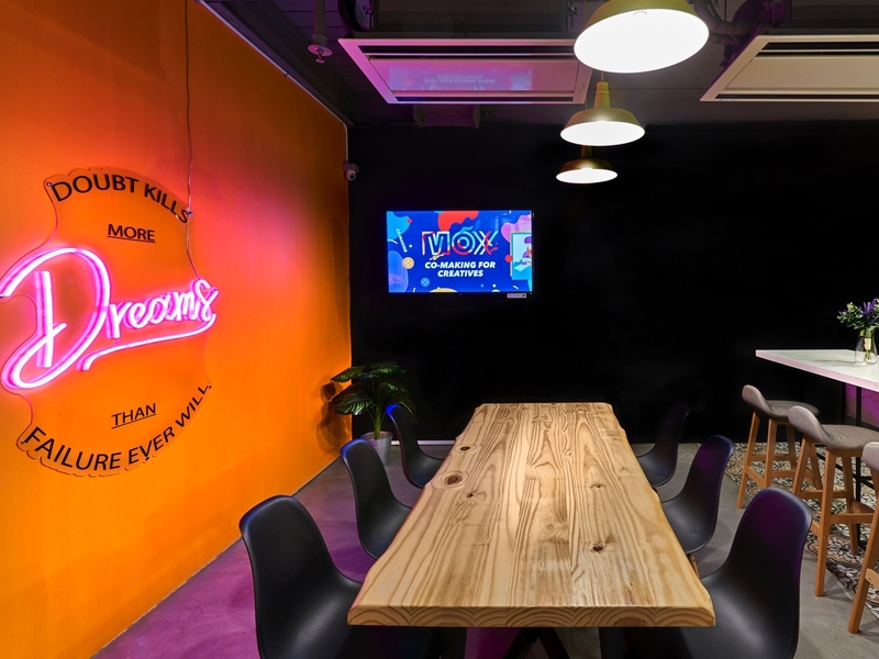 singapore coworking space with black-orange meeting room and wooden table